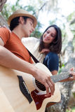 Young man playing guitar for woman in trees Royalty Free Stock Photography
