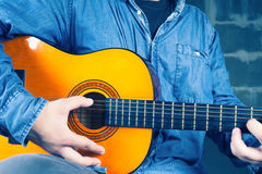 Young man playing on a guitar. Royalty Free Stock Photo