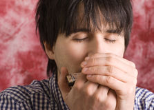 Young man playing harmonica Stock Photos