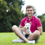 Young man playing with his dog in the park Royalty Free Stock Images