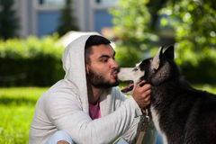 Young man playing with his husky dog in park Stock Photos