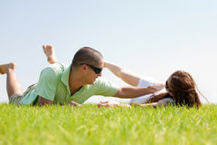Young man playing with his wife on a grass. Lawn and laying down Stock Photography