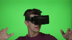 Young man playing a horror adventure game using a VR virtual reality headset on chroma key background - stock video footage