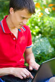 Young man is playing on laptop. Outdoor shoot Stock Photography