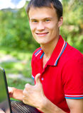 Young man is playing on laptop. And showing thumb up sign, outdoor shoot Stock Photos
