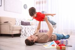 Young man playing with little son at home on Father`s Day. Young men playing with his little son at home on Father`s Day Royalty Free Stock Photos