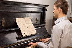 Young man playing music on a wooden piano Royalty Free Stock Image