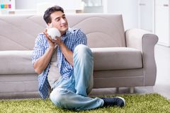 The young man playing with pet rabbit at home Stock Images