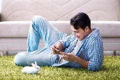 The young man playing with pet rabbit at home. Young man playing with pet rabbit at home Royalty Free Stock Photography