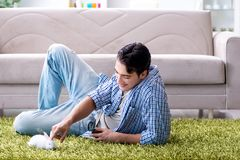 The young man playing with pet rabbit at home. Young man playing with pet rabbit at home Stock Photography