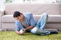 The young man playing with pet rabbit at home. Young man playing with pet rabbit at home Royalty Free Stock Photos