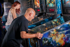 Young man playing pinball Stock Image