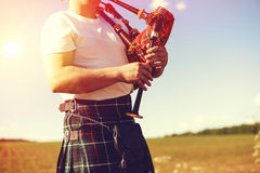 Young man playing pipes in national uniform on Stock Photos