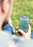 Young man playing Pokemon Go in the park Royalty Free Stock Images