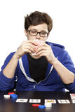 Young man playing poker. At table hiding behind cards Royalty Free Stock Images