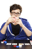 Young man playing poker. At table hiding behind cards Royalty Free Stock Photo