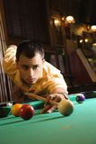 Young man playing pool. Young man concentrating while aiming at pool ball while playing billiards stock images