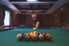 Young man playing billiard indoors. Spending free time on gambling Royalty Free Stock Photos
