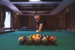Young man playing billiard indoors. Spending free time on gambling. Young man playing pool billiard indoors. Spending free time on gambling Royalty Free Stock Photos