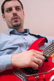 Young man Playing a red guitar Royalty Free Stock Photography