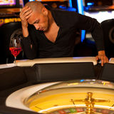 Young man playing roulette in casino betting and loosing money Royalty Free Stock Photography