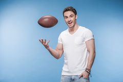 Young man playing with rugby ball and smiling at camera Stock Photography