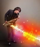 Young man playing on saxophone with colorful sound waves Royalty Free Stock Images