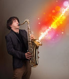 Young man playing on saxophone with colorful sound waves Stock Photography