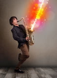 Young man playing on saxophone with colorful sound waves Royalty Free Stock Image