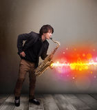 Young man playing on saxophone with colorful sound waves Stock Images