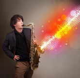 Young man playing on saxophone with colorful sound waves Stock Photos