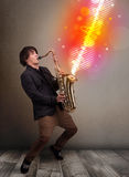 Young man playing on saxophone with colorful sound waves Stock Photo