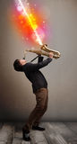 Young man playing on saxophone with colorful sound waves Royalty Free Stock Photo