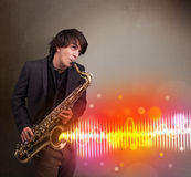 Young man playing on saxophone with colorful sound waves Royalty Free Stock Photos
