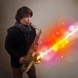 Young man playing on saxophone with colorful sound waves Royalty Free Stock Photography