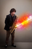 Young man playing on saxophone with colorful sound waves. Attractive young man playing on saxophone with colorful sound waves Royalty Free Stock Photography