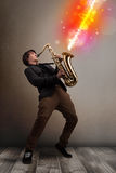 Young man playing on saxophone with colorful sound waves. Attractive young man playing on saxophone with colorful sound waves Royalty Free Stock Photo