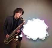 Young man playing on saxophone with copy space in white cloud Stock Image