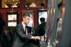 Young man playing the slot machine Stock Images