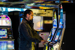 Young man playing at slot machine Royalty Free Stock Images