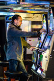 Young man playing at slot machines Royalty Free Stock Photos