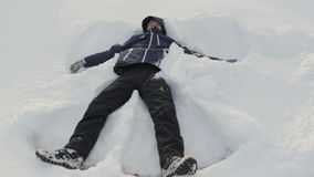 Young man is playing in snow under the sun, making snow angel, having fun, smiling. Winter vacation, holidays stock video