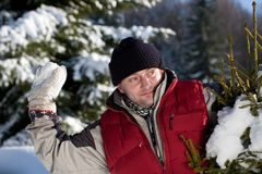Young man playing with snowball Stock Images