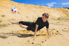 Young man playing soccer on beach Stock Photo