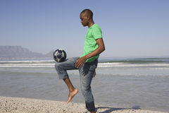 Young Man Playing Soccer On Beach. Side view of a young African American man playing soccer on beach Royalty Free Stock Photos