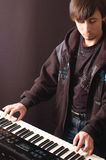 Young man playing on a synthesizer. A young man playing on a synthesizer on a dark background Stock Photography