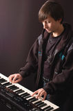 Young man playing on a synthesizer. A young man playing on a synthesizer on a dark background Royalty Free Stock Photo