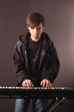 Young man playing on a synthesizer. A young man playing on a synthesizer on a dark background Royalty Free Stock Photos