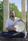 Young man playing the tambourine outdoors Royalty Free Stock Images