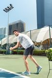 Young man playing tennis outdoors in a modern district of the city stock photo